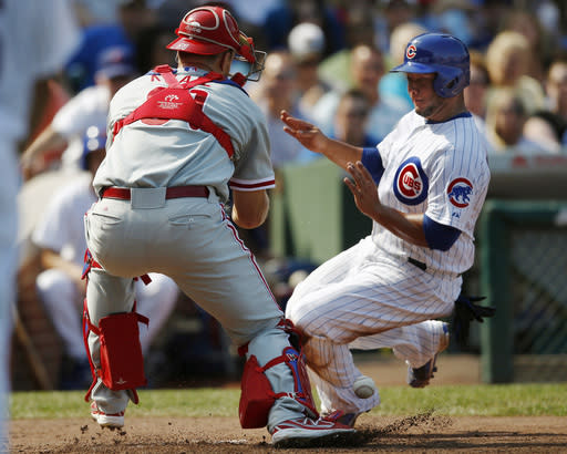 Chicago Cubs' Welington Castillo safely reaches home as Philadelphia Phillies catcher Erik Kratz looses the ball during the fourth inning of a baseball game on Sunday, Sept. 1, 2013, in Chicago. (AP Photo/Andrew A. Nelles)