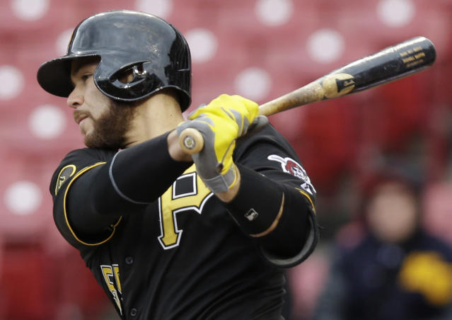 Pittsburgh Pirates' Russell Martin follows through on a hit off Cincinnati Reds relief pitcher Sam LeCure on Tuesday, April 15, 2014, in the seventh inning of a baseball game that was suspended by rain Monday in Cincinnati. (AP Photo/Al Behrman)