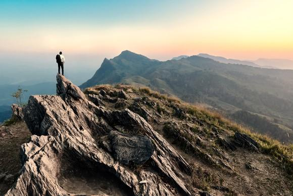 A person stands on top of a mountain staring at a mountain range in the distance.