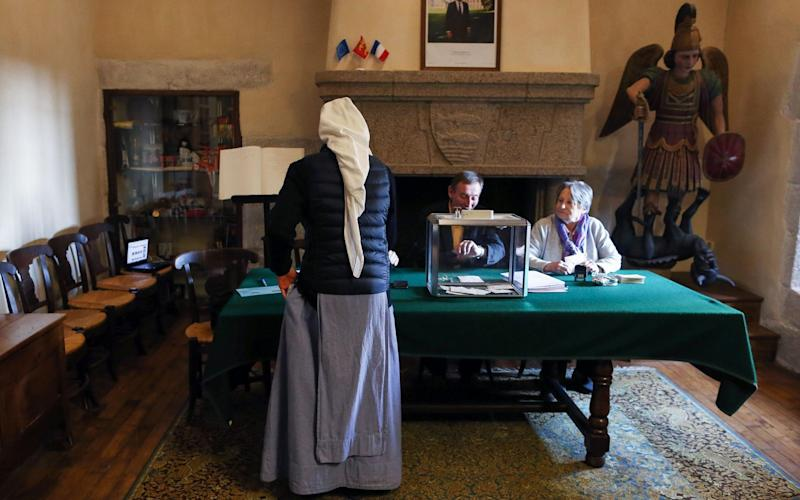A nun of the Monastic of the Fraternities of Jerusalem casts her ballot at a polling station in Le Mont-Saint-Michel, northwestern France - Credit:  CHARLY TRIBALLEAU/AFP