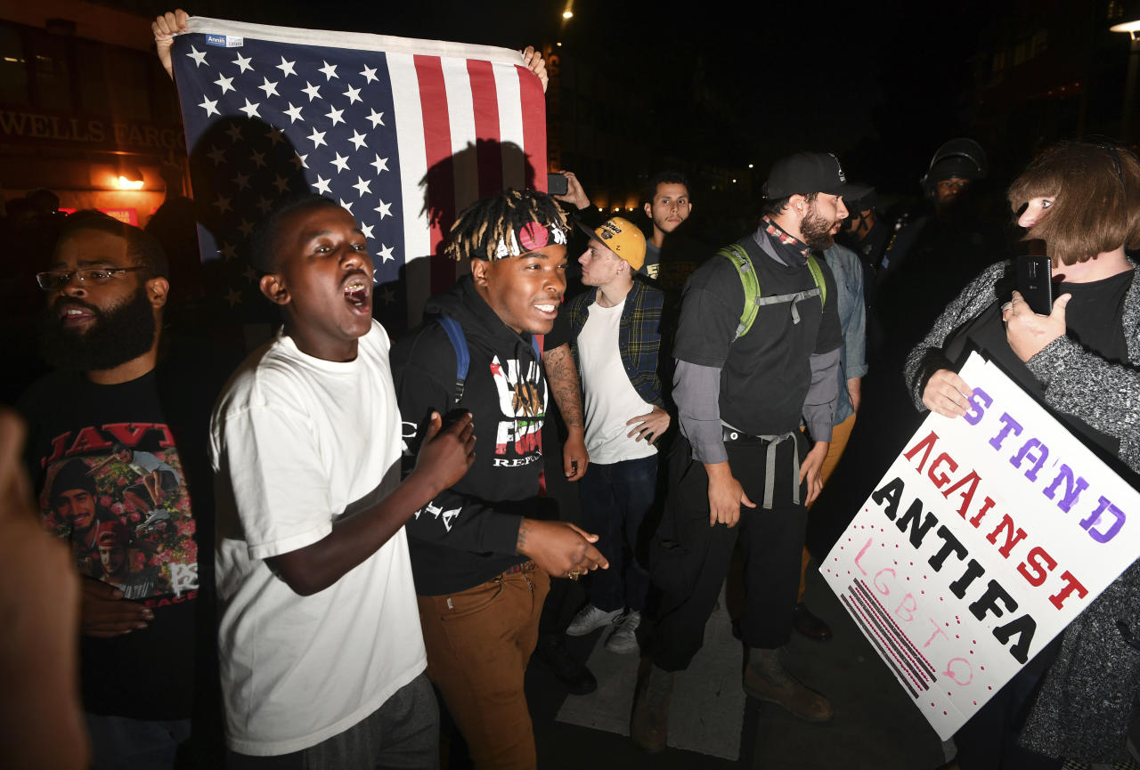 Amber Cummings, right, holds a sign as Phoenix Jones, in white shirt, and Morris Black , center, shout during a protest outside of a speaking engagement by Ben Shapiro on the campus of the University of California Berkeley in Berkeley, Calif., Thursday, Sept. 14, 2017. Several streets around the University of California, Berkeley, were closed off Thursday with concrete and plastic barriers ahead of an evening appearance by the conservative commentator - the latest polarizing event to raise concerns of violence on the famously liberal campus. (AP Photo/Josh Edelson)