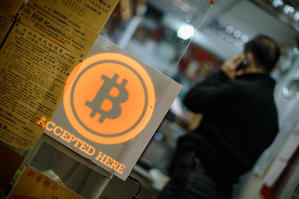 A man talks on a mobile phone in a shop displaying a bitcoin sign during the opening ceremony of the first bitcoin retail shop in Hong Kong (AFP/Getty)