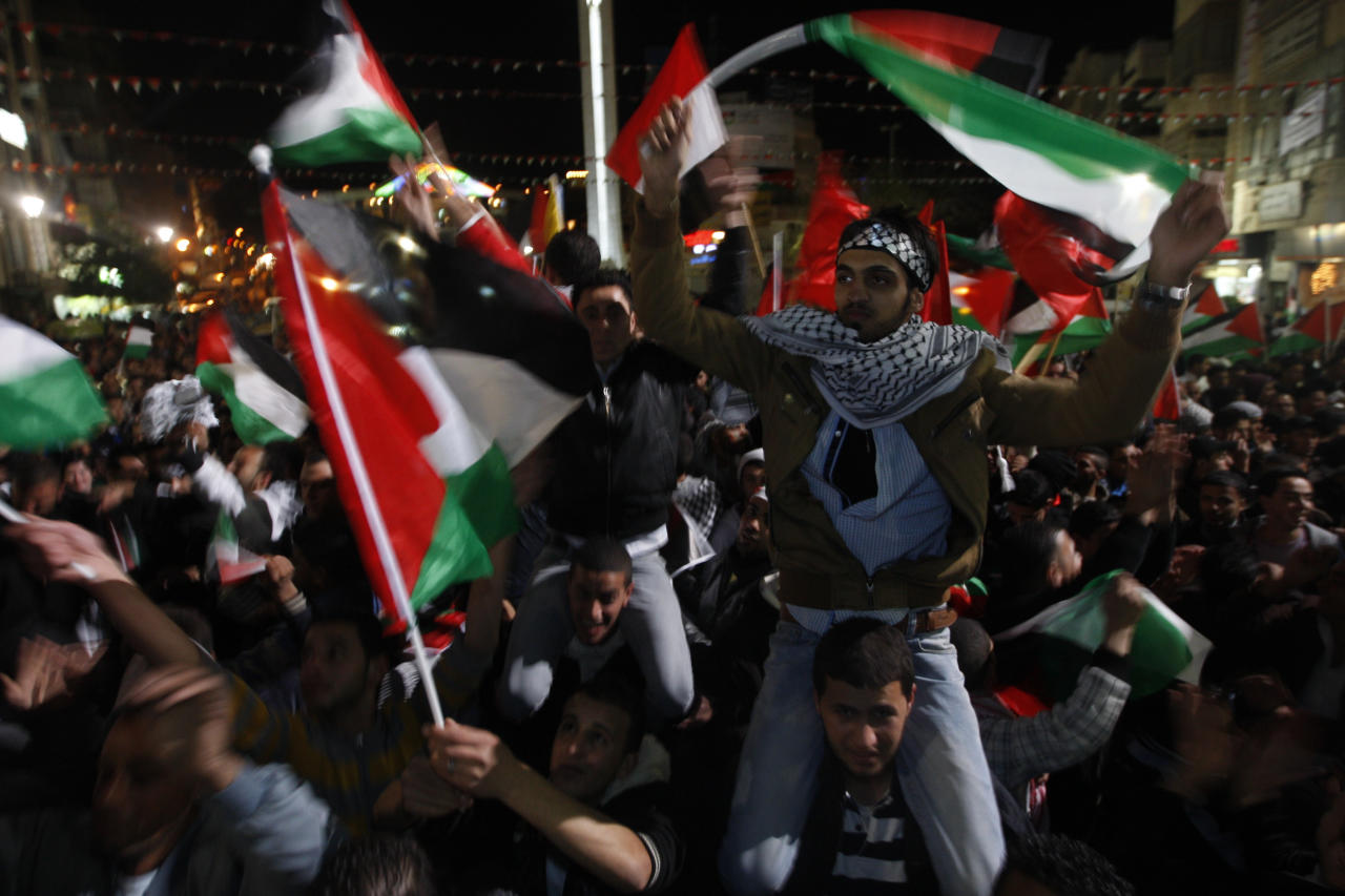 Palestinians wave Palestinian flags as they watch a large screen showing the U.N. General Assembly votes on a resolution to upgrade the status of the Palestinian Authority to a nonmember observer state, In the west bank city of Ramallah, Thursday, Nov. 29, 2012. The U.N. General Assembly has voted by a more than two-thirds majority to recognize the state of Palestine. The resolution upgrading the Palestinians' status to a nonmember observer state at the United Nations was approved by the 193-member world body late Thursday by a vote of 138-9 with 41 abstentions. (AP Photo/Majdi Mohammed)