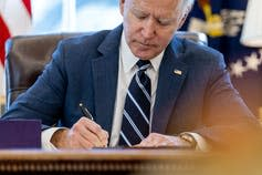 Joe Biden signs a bill at his desk in the Oval Office.