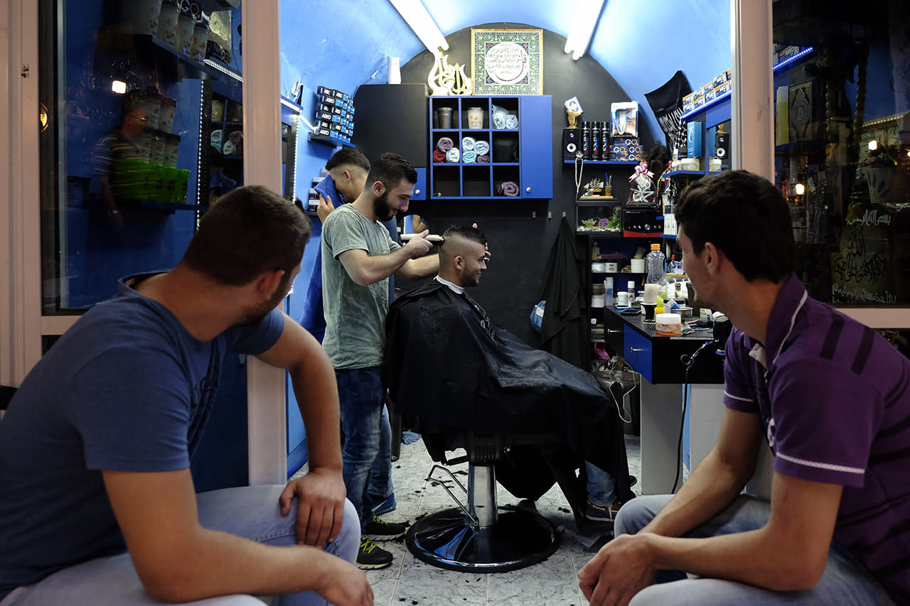 <p>A young Palestinian man gets a haircut in a barber shop while others watch and wait in East Jerusalem. </p>