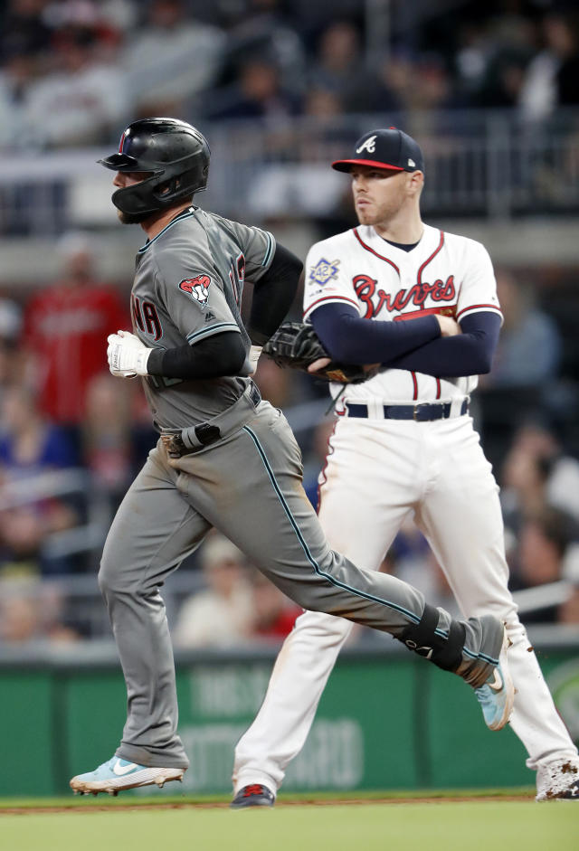 Arizona Diamondbacks' Christian Walker (53) runs past Atlanta Braves first baseman Freddie Freeman (5) as he rounds the bases after hitting a home run in the ninth inning of a baseball game, Tuesday, April 16, 2019, in Atlanta. Arizona won 9-6. (AP Photo/John Bazemore)