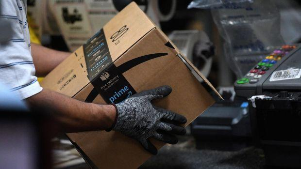 A worker assembles a box for delivery at the Amazon fulfillment center