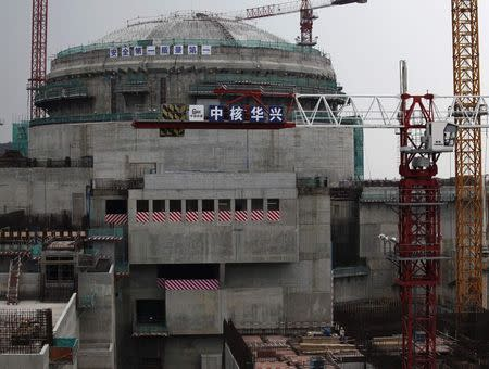 Workers stand in front of a nuclear reactor under construction in Taishan, China