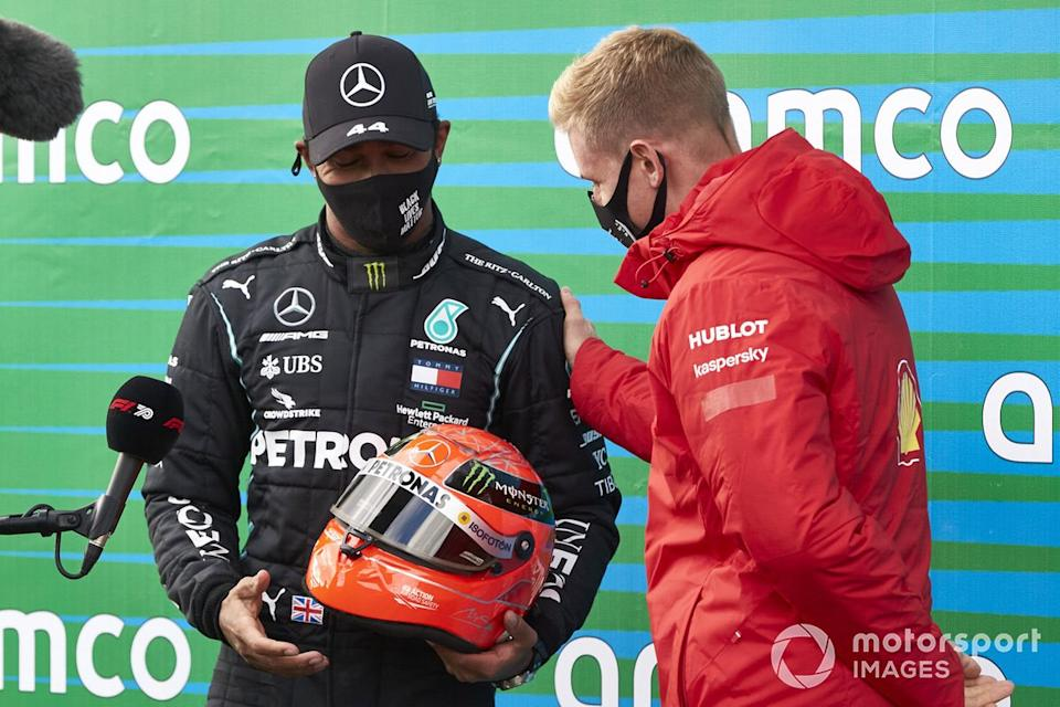"""Mick Schumacher presents Lewis Hamilton, Mercedes-AMG F1, 1st position, with his fathers helmet after the Mercedes driver equalled Michael Schumachers record 91 race wins<span class=""""copyright"""">Steve Etherington / Motorsport Images</span>"""