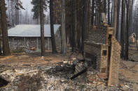 FILE - In this Sept. 2, 2021 file photo a cabin partially covered in fire-resistant material stands next to properties destroyed in the Caldor Fire in Twin Bridges, Calif. Aluminum wraps designed to protect homes from flames are getting attention as wildfires burn in California. (AP Photo/Jae C. Hong,File)