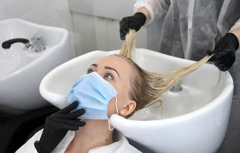 MOSCOW, RUSSIA - JUNE 9, 2020: A worker of the Starlett beauty salon tends to her colleague as they prepare for the reopening. Starting from 9 June, Moscow's beauty and hair salons, which were closed due to the COVID-19 pandemic, resume operation. Valery Sharifulin/TASS (Photo by Valery Sharifulin\TASS via Getty Images)
