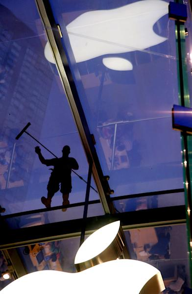 FILE - In this July 21, 2011 file photo, a window washer works atop the cube-like structure of glass that houses the Apple Store showroom in the Upper West Side of Manhattan. Apple Inc. said it will announce the outcome of its internal discussion concerning its enormous cash balance on Monday morning, March 19, 2012. (AP Photo/Craig Ruttle, File)