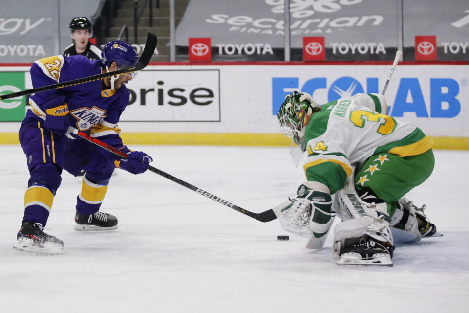 Los Angeles Kings left wing Andreas Athanasiou (22) is stopped by Minnesota Wild goaltender Kaapo Kahkonen (34) in the first period during an NHL hockey game, Saturday, Feb. 27, 2021, in St. Paul, Minn. (AP Photo/Andy Clayton-King)
