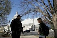 United States Capitol police officer Harry Dunn (L) checks identification from a pedestrian in front of the U.S. Capitol in Washington March 29, 2016. REUTERS/Gary Cameron
