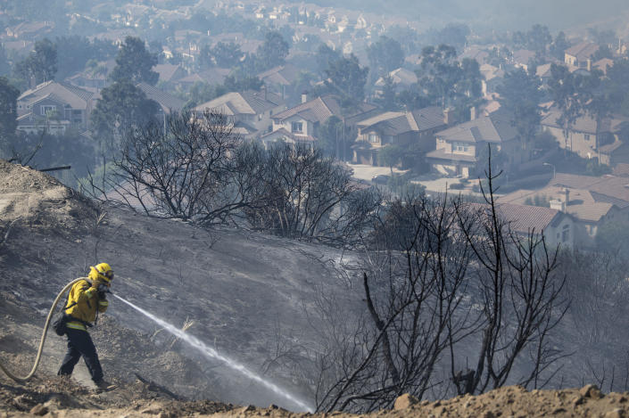 Firefighters work flames from the Silverado fire atop a hill above homes in Foothill Ranch where a mandatory evacuation is in place on Tuesday, Oct. 27, 2020, because of (Mindy Schauer/The Orange County Register via AP)
