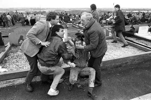 An injured man is aided by mourners, including Sinn Fein vice president Martin McGuinness, left, at Milltown Cemetery