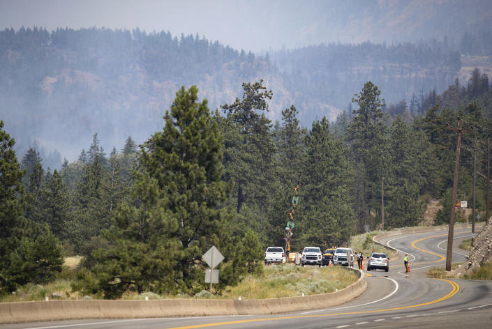 Royal Canadian Mounted Police (RCMP) officers man a roadblock on the Trans-Canada Highway as a wildfire burns in Lytton, British Columbia, Friday, July 2, 2021. Officials on Friday hunted for any missing residents of a British Columbia town destroyed by wildfire as Canadian Prime Minister Justin Trudeau offered federal assistance. (Darryl Dyck/The Canadian Press via AP)