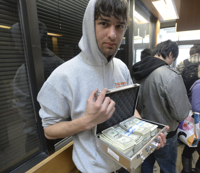 University of Utah student Luke Mughal holds a briefcase full of one-dollar bills as he waits in a long line to pay his tuition at the Student Services Building on the University of Utah campus in Salt Lake City, Utah Tuesday, Jan. 21, 2014. Mughal is paying his tuition in one-dollar bills to protest the high cost of tuition. (AP Photo/The Salt Lake Tribune, Steve Griffin)