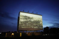 """An image of devastation from the Tulsa Race Massacre is shown on a drive-in screen from a documentary called """"Rebuilding Black Wall Street,"""" during a screening of documentaries during centennial commemorations of the Tulsa Race Massacre, Wednesday, May 26, 2021, in Tulsa, Okla. (AP Photo/John Locher)"""