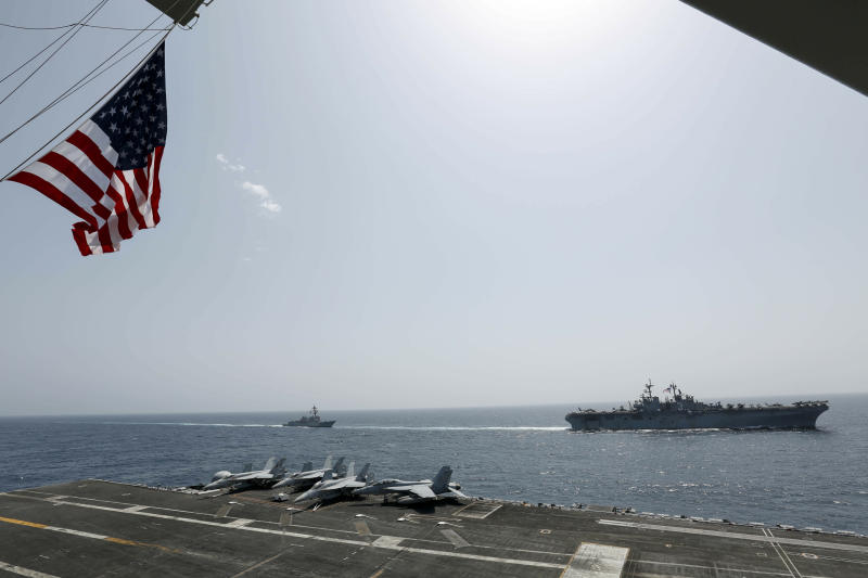 "CORRECTS DATE - In this Friday, May 17, 2019, photo, released by the U.S. Navy, the amphibious assault ship USS Kearsarge, right, and the Arleigh Burke-class guided-missile destroyer USS Bainbridge, left, are seen from the Nimitz-class aircraft carrier USS Abraham Lincoln as they sail in the Arabian Sea. Commercial airliners flying over the Persian Gulf risk being targeted by ""miscalculation or misidentification"" from the Iranian military amid heightened tensions between the Islamic Republic and the U.S., American diplomats warned Saturday, May 18, 2019, even as both Washington and Tehran say they don't seek war. (Mass Communication Specialist Seaman Michael Singley, U.S. Navy via AP)"