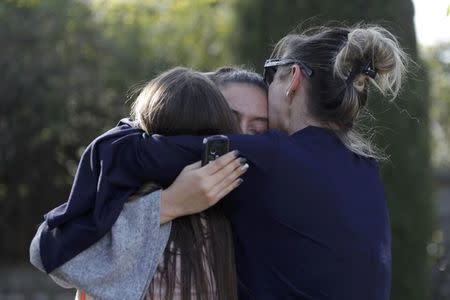 People embrace near the Tocqueville high school after a shooting has taken place injuring at least eight people, in Grasse, southern France
