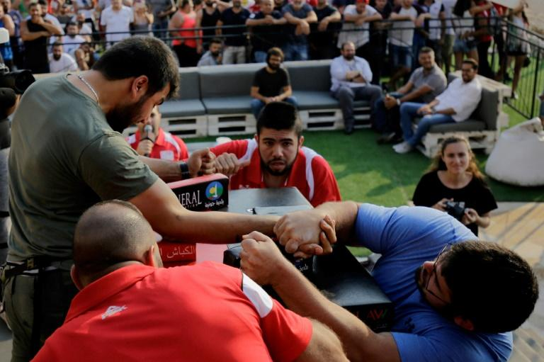 Watched closely by judges, Lebanese men compete in an arm wrestling championship in the coastal city of Jounieh on July 13, 2018