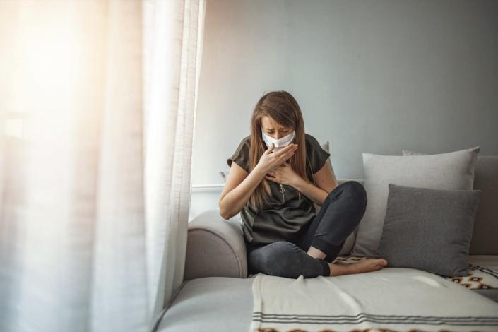 Woman wearing surgical mask on face protective for spreading of disease Covid-19 pandemic.. Girl symptom cough while sitting on Sofa.