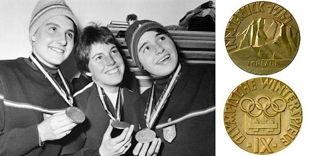 <p>The 1964 medal design for the IX Winter Olympic Games features an Alpine scene. The 1964 Winter Olympics were held in Innsbruck, Austria.<br>(Women's Giant Slalom winners, (L-R) France's Christine Goitschell (gold), USA's Jean Saubert (bronze), France's Marielle Goitschell (silver)/Getty Images; IOC photo) </p>