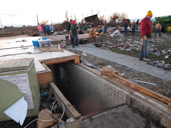 Friends and neighbors comb the rubble of Curt Zehr's home just outside Washington, Ill., on Sunday, Nov. 17, 2013. Zehr's wife and adult son took shelter in the basement at the base of the pictured stairs as a tornado destroyed their farm house. They were not injured. The tornado cut a path of destruction through Washington. (AP Photo/David Mercer)