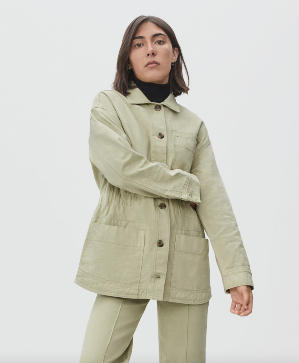 model with brown hair posing in Everlane The Cinchable Chore Jacket in Sage and green pants