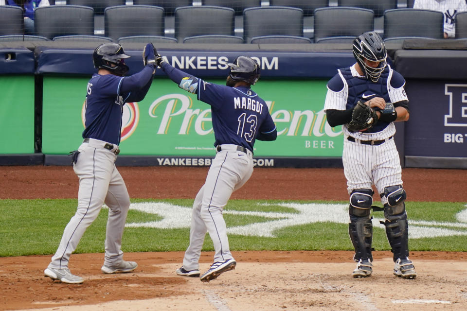 New York Yankees catcher Gary Sanchez, right, reacts as Tampa Bay Rays' Manuel Margot, center, celebrates with Austin Meadows after they scored on a two-run home run by Margot during the fourth inning of a baseball game Saturday, April 17, 2021, in New York.(AP Photo/Frank Franklin II)