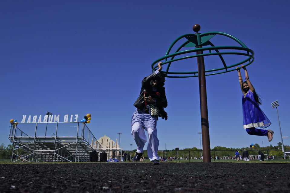 Saif Chaudhry plays with his daughter Ariana Chaudhry, 8, on playground near the site of an outdoor celebration of Eid al-Fitr in Overpeck County Park in Ridgefield Park, N.J., Thursday, May 13, 2021. Millions of Muslims across the world are marking a muted and gloomy holiday of Eid al-Fitr, the end of the fasting month of Ramadan - a usually joyous three-day celebration that has been significantly toned down as coronavirus cases soar. (AP Photo/Seth Wenig)