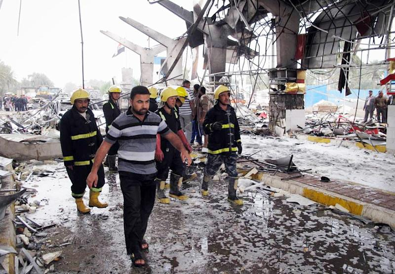 Fire fighters and civilians inspect the site of a massive bomb attack in Hillah, about 60 miles (95 kilometers) south of Baghdad, Iraq, Sunday, March 9, 2014. A suicide car bomber set off his explosive-laden vehicle at a security checkpoint in southern Iraq on Sunday, killing and wounding scores of people, police said. Iraq has seen a spike in violence since last April, with the death toll climbing to its highest levels since the worst of the country's sectarian bloodletting in 2006-2008. The U.N. says 8,868 people were killed in 2013, and more than 1,400 people were killed in January and February of this year. (AP Photo/Str)