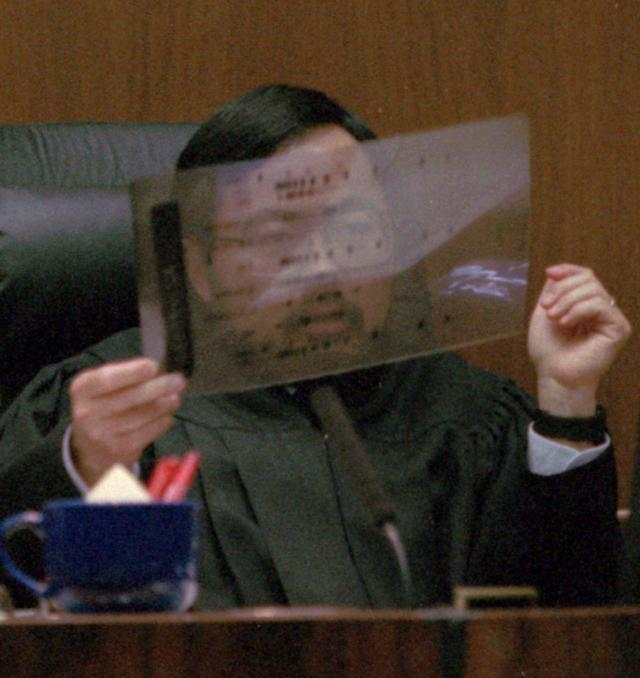 <p>Judge Lance Ito holds up a sample of a DNA sequence during the trial. The prosecution built its case largely around DNA evidence they said linked O.J. Simpson to the crime scene. But the defense raised questions about the reliability of the blood evidence; arguing it had been mishandled by police. (Photo: John McCoy/AP) </p>