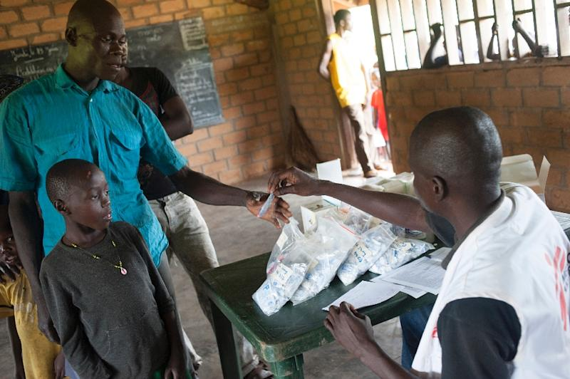 A nurse gives medicine to a father to treat the malaria of his child in a hospital near Bambari, on July 27, 2014 (AFP Photo/Andoni Lubaki)