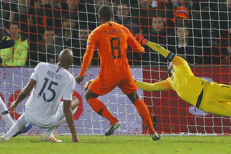 Netherlands' Georginio Wijnaldum, center, scores his side's first goal passing France's goalkeeper Hugo Lloris, right, during the international friendly soccer match between The Netherlands and France at De Kuip stadium in Rotterdam, Netherlands, Friday, Nov. 16, 2018. (AP Photo/Peter Dejong)