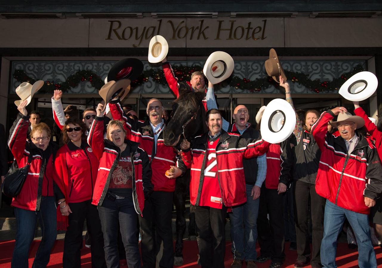 Fletcher Armstrong and the Calgary Grey Cup committee, give a cheer after Marty the horse visited the Royal York Hotel front foyer on Thursday, Nov. 22, 2012 in Toronto. Calgary Stampeders will play the Toronto Argonauts in the Canadian Football League Grey Cup Sunday, Nov. 25, 2012. THE CANADIAN PRESS/Sean Kilpatrick