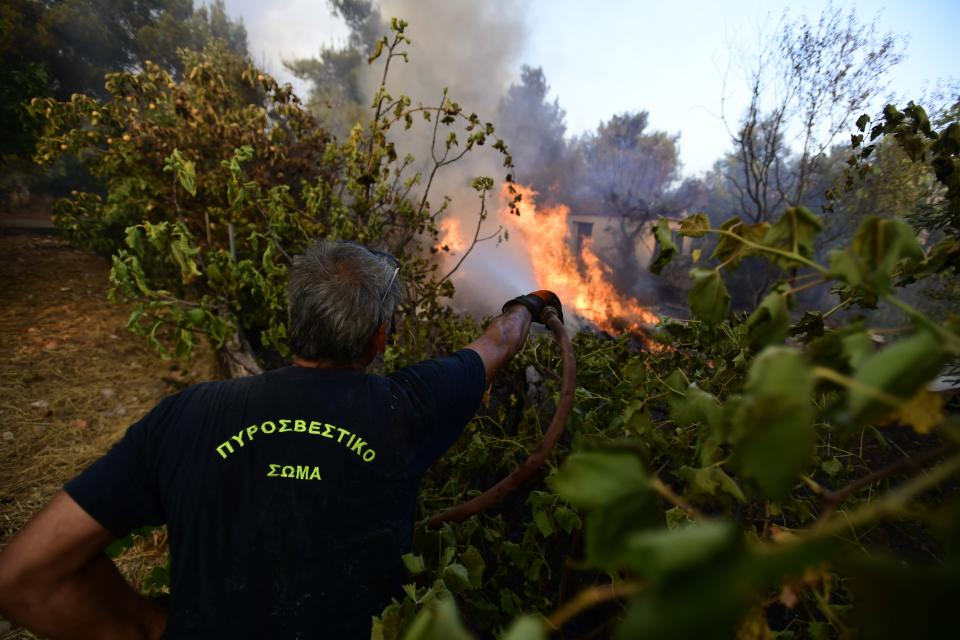A firefighter tries to extinguish a fire in Kryoneri area, northern Athens, Greece, Thursday, Aug. 5, 2021. Wildfires rekindled outside Athens and forced more evacuations around southern Greece Thursday as weather conditions worsened and firefighters in a round-the-clock battle stopped the flames just outside the birthplace of the ancient Olympics. (AP Photo/Michael Varaklas)