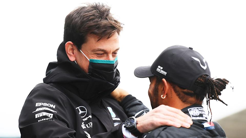 Mercedes team principal Toto Wolff is seen here chatting with driver Lewis Hamilton.