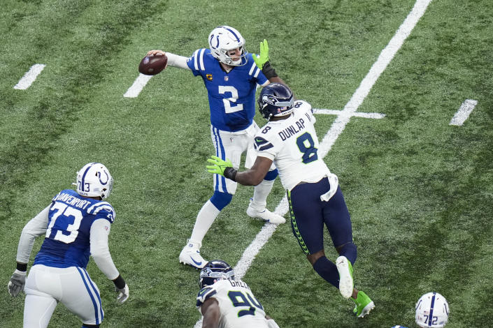 Indianapolis Colts quarterback Carson Wentz (2) is pressured by Seattle Seahawks defensive end Carlos Dunlap (8) during the second half of an NFL football game in Indianapolis, Sunday, Sept. 12, 2021. (AP Photo/AJ Mast)