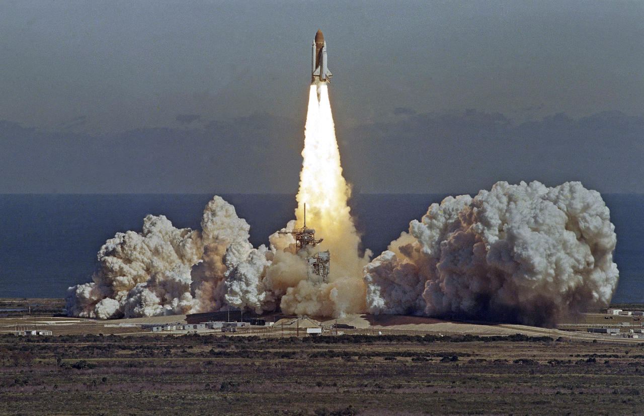 The Space Shuttle orbiter Challenger lifts off from Kennedy Space Center, Florida, Jan. 28, 1986, in a cloud of smoke with a crew of seven aboard. The shuttle exploded after this photo, taken from atop the Vehicular Assembly Building, was made. (AP Photo/Thom Baur)