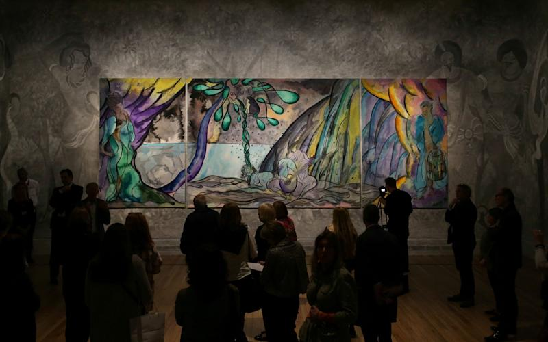 Visitors view the British artist Chris Ofili's tapestry 'The Caged Bird's Song' at the 'Weaving Magic' exhibition at the National Gallery in April - AFP
