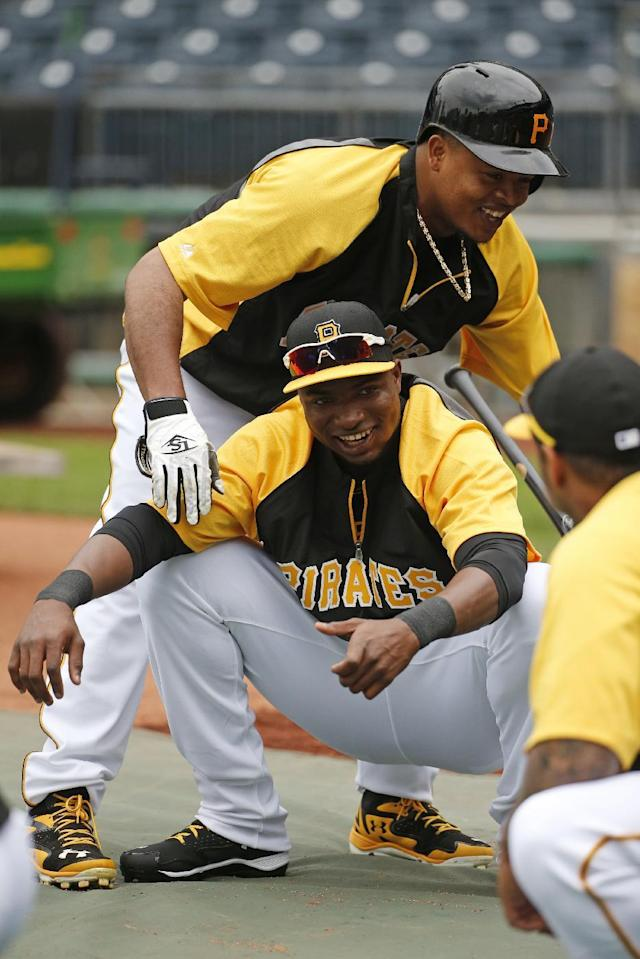 Pittsburgh Pirates' Gregory Polanco, bottom, is welcomed by Pittsburgh Pirates starting pitcher Edinson Volquez as he stretches during warm ups before a baseball game against the Chicago Cubs in Pittsburgh Tuesday, June 10, 2014. It will be Polanco's Major League debut. (AP Photo/Gene J. Puskar)