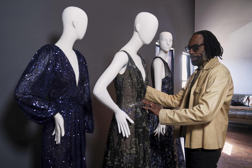 """Fashion designer Kevan Hall pauses for a picture with his """"Galaxy Collection"""" at his haute couture atelier in West Los Angeles Thursday, March 18, 2021. A year ago, Hall quickly moved away from his trademark gowns and cocktail dresses to caftans, tunics and pull-on pants. Now Hall is adding back some dressier looks, but he's eliminating the full skirts and scaling back the beading in favor of simple gowns and dresses in knit and tulle fabrics. (AP Photo/Damian Dovarganes)"""