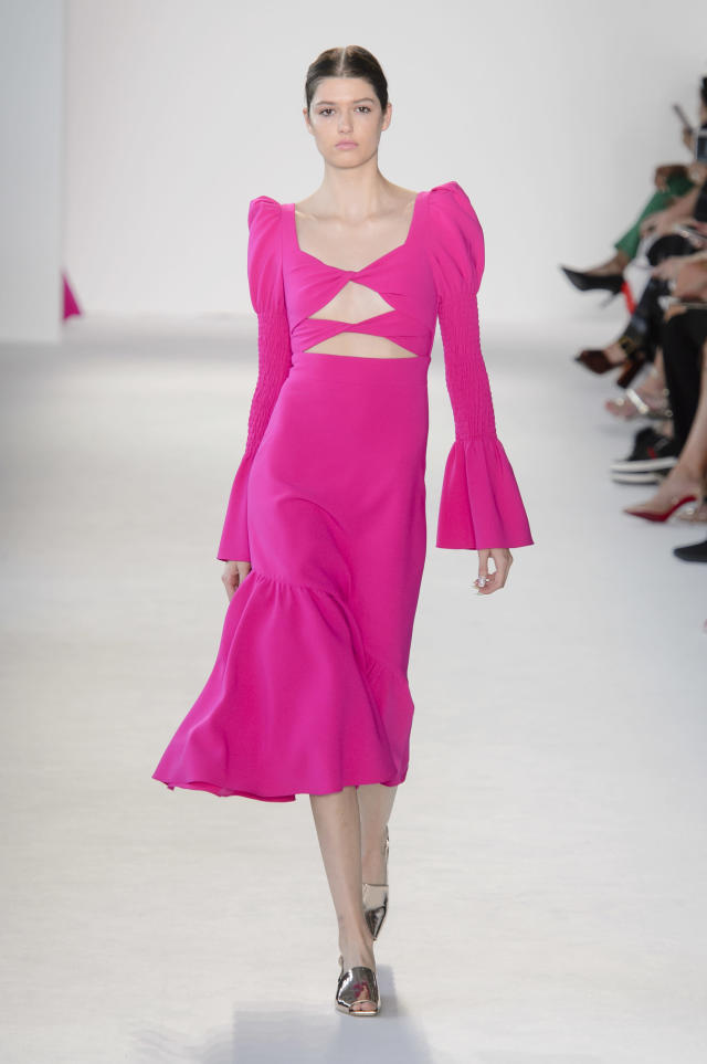 <p><i>Model wears a hot pink, bell-sleeve shoulder with cutouts from the SS18 Christian Siriano collection. (Photo: ImaxTree) </i></p>