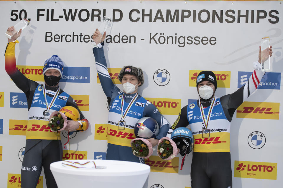 Felix Loch of Germany, Roman Repilov of Russia and David Gleirscher of Austria present their trophys during the victory ceremony after the men's race at the Luge World Championships in Koenigssee, Germany, Saturday Jan. 30, 2021. (AP Photo/Andreas Schaad)