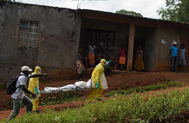 Health workers from the Sierra Leone's Red Cross Society Burial Team 7 remove a corpse from a house in Freetown on November 12, 2014 (AFP Photo/Francisco Leong)