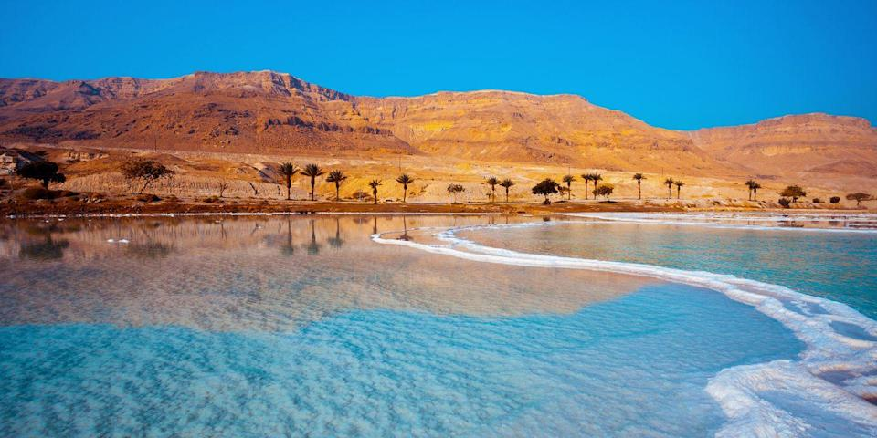 """<p>The <a href=""""https://www.tripadvisor.com/Attraction_Review-g293979-d319238-Reviews-Dead_Sea-Dead_Sea_Region.html"""" rel=""""nofollow noopener"""" target=""""_blank"""" data-ylk=""""slk:Dead Sea"""" class=""""link rapid-noclick-resp"""">Dead Sea</a>, on the border between Israel and Jordan, is not only the lowest point on earth, but it's also the saltiest body of water in the world — its salinity and minerals provide buoyancy for floating, which is super fun! Floating in the bright blue waters of this ancient lake (it's not actually a sea), surrounded by the Negev Desert, is quite the sight.</p>"""