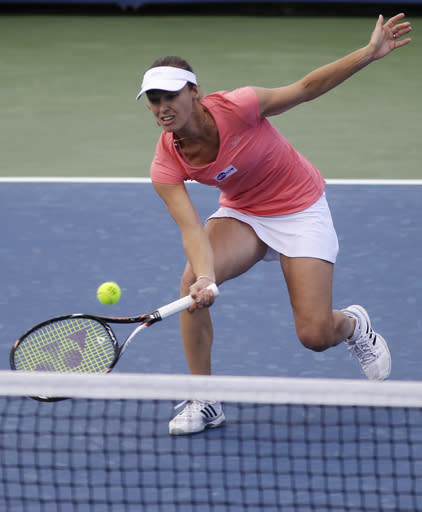 Martina Hingis, from Switzerland, volleys during a doubles match with partner Daniela Hantuchova, from Slovakia, against Sara Errani and Roberta Vinci, from Italy, at the Western & Southern Open tennis tournament, Wednesday, Aug. 14, 2013, in Mason, Ohio. (AP Photo/Al Behrman)