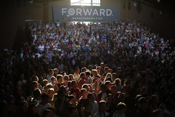 Late afternoon light streams in to illuminate part of the crowd cheering U.S. President Barack Obama during a campaign rally at the Iowa State Fairgrounds in Des Moines, Iowa May 24, 2012.